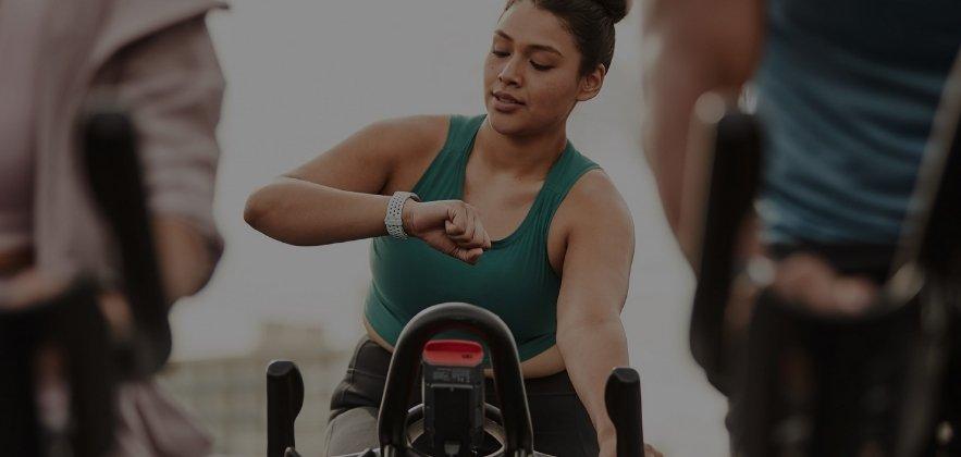 women on a stationary bike best fitbit for women